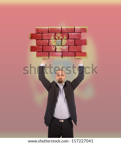 Businessman holding a large piece of a brick wall, flag of Montenegro, isolated on national flag - stock photo