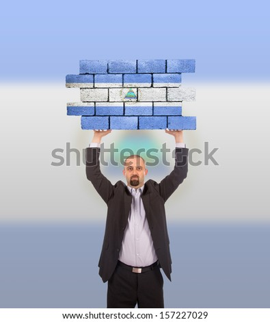 Businessman holding a large piece of a brick wall, flag of Nicaragua, isolated on national flag - stock photo
