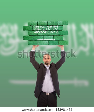Businessman holding a large piece of a brick wall, flag of Saudi Arabia, isolated on national flag - stock photo