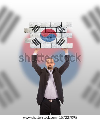 Businessman holding a large piece of a brick wall, flag of South Korea, isolated on national flag - stock photo