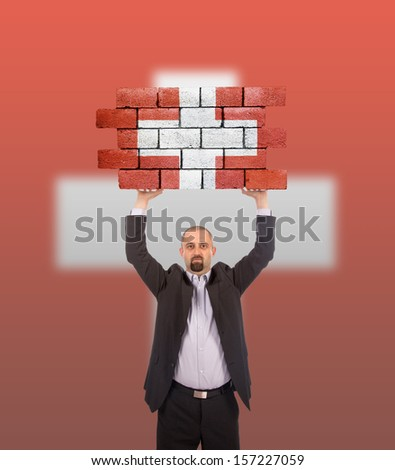 Businessman holding a large piece of a brick wall, flag of Switzerland, isolated on national flag - stock photo