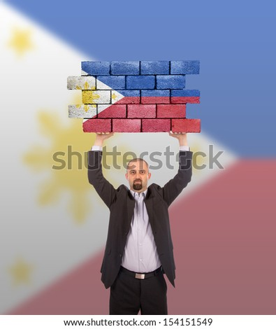 Businessman holding a large piece of a brick wall, flag of the Philippines, isolated on national flag - stock photo