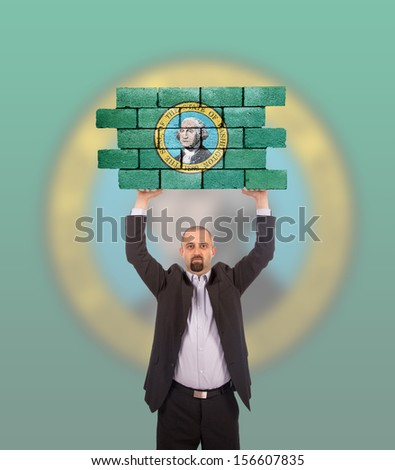 Businessman holding a large piece of a brick wall, flag of Washington, isolated on national flag - stock photo