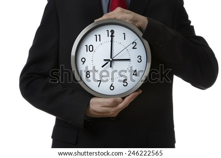 Businessman holding a large wall clock up to his body  - stock photo