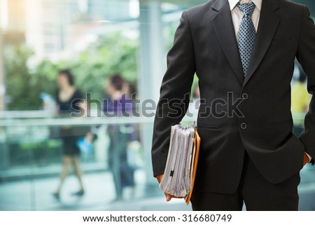 Businessman holding a lot of resume data waiting for job interview - stock photo