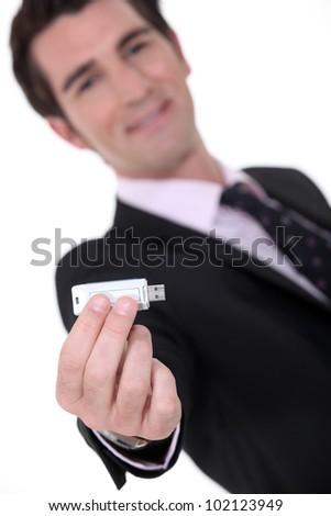 Businessman holding a memory stick - stock photo