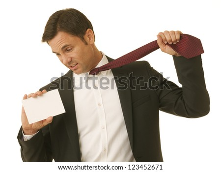 Businessman holding a message card while pulling on his necktie - stock photo