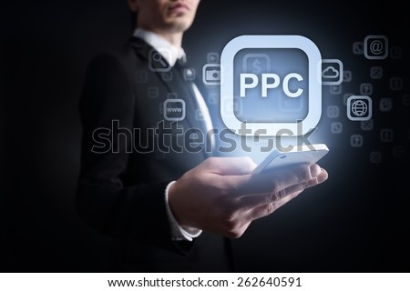 businessman holding a mobile phone with applications icons and ppc text on virtual screen. Internet concept. business concept - stock photo