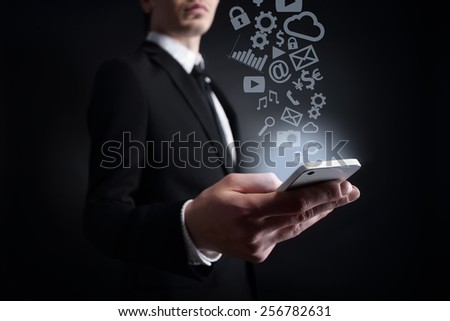 businessman holding a mobile phone  with applications icons. Internet concept. business concept. - stock photo