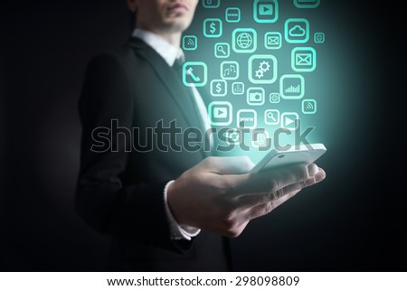 businessman holding a mobile phone with applications icons on virtual screen. Internet concept. business concept.