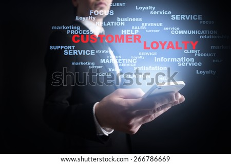 Businessman holding a mobile phone with customer loyalty text on virtual screen. Internet concept. Business concept. - stock photo