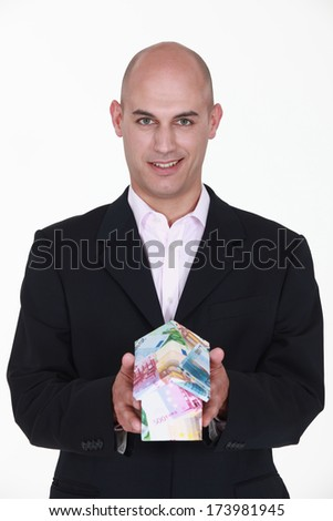 businessman holding a model of house made of money - stock photo