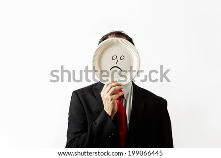 businessman holding a paper plate up to his face with a sad face draw on plate - stock photo