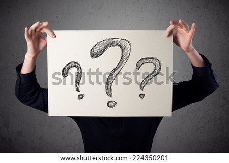 Businessman holding a paper with drawed question marks on it in front of his head - stock photo