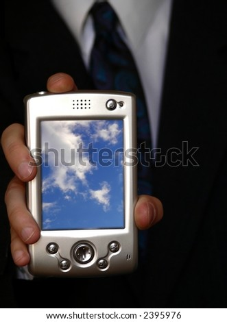 businessman holding a pda with blue cloudy sky on the screen - stock photo