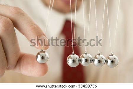 businessman holding a pendulum ball - stock photo