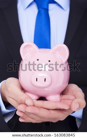 Businessman holding a piggy bank - stock photo