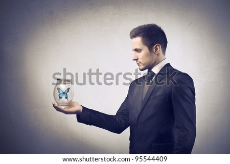 Businessman holding a pot with butterfly in it - stock photo