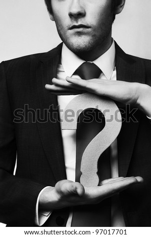 businessman holding a question mark between his hands - stock photo