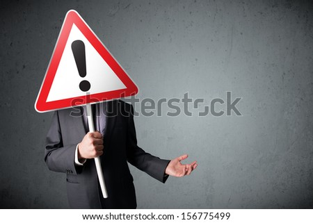 Businessman holding a red traffic triangle warning sign in front of his head - stock photo