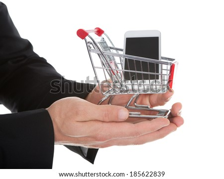 Businessman holding a shopping cart and tablet cupped in his hands conceptual of e-commerce and online shopping  isolated on white