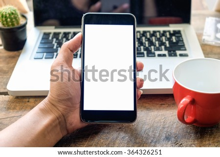 businessman holding a smart phone on wood table at office - stock photo