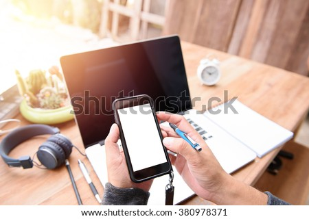 Businessman holding a smart phone with white screen.on a desk outdoors. One corner of the house With the morning light - stock photo