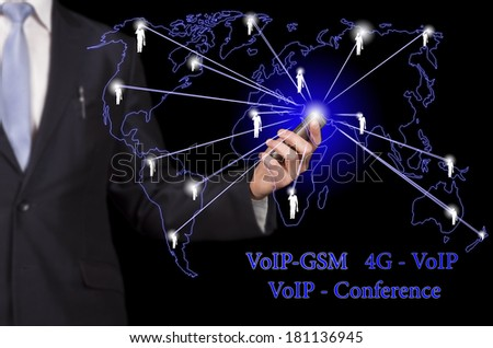 "businessman holding a smartphone in hand, linking business and social networks with the inscription ""VOIP - GSM"", ""4G-VOIP"", ""VOIP Conference"" - stock photo"