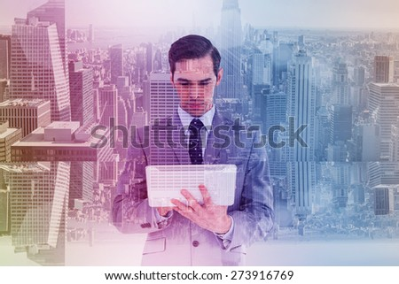 Businessman holding a tablet computer against room with large window looking on city - stock photo