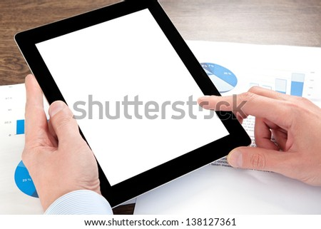 businessman holding a tablet computer with isolated screen on the table with graphics - stock photo