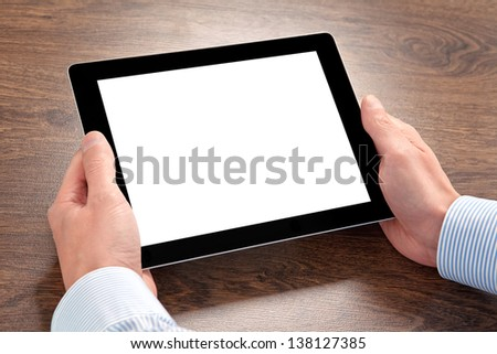 businessman holding a tablet computer with isolated screen  over the villages table - stock photo