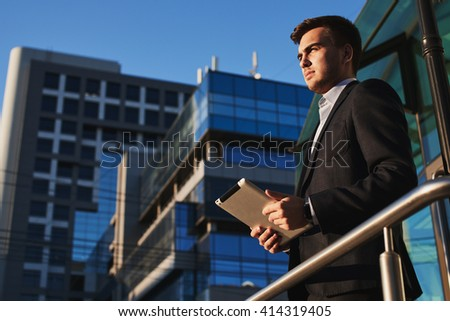 Businessman holding a tablet in hands on the background of buildings with glass facades