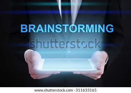 """Businessman holding a tablet pc with """"Brainstorming"""" text on virtual screen. Internet concept. Business concept. - stock photo"""