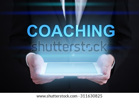 "Businessman holding a tablet pc with ""Coaching"" text on virtual screen. Internet concept. Business concept."