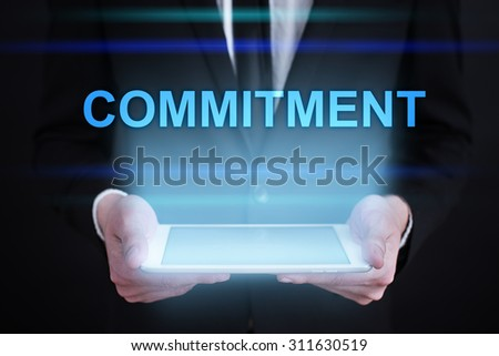 "Businessman holding a tablet pc with ""Commitment"" text on virtual screen. Internet concept. Business concept."