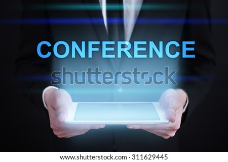 "Businessman holding a tablet pc with ""Conference"" text on virtual screen. Internet concept. Business concept."