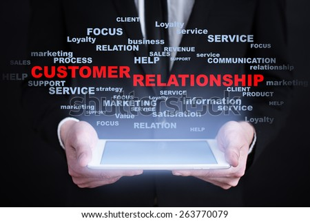 Businessman holding a tablet pc with customer relationship text on virtual screen. Internet concept. Business concept. - stock photo