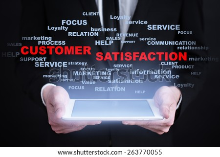 Businessman holding a tablet pc with customer satisfaction text on virtual screen. Internet concept. Business concept. - stock photo