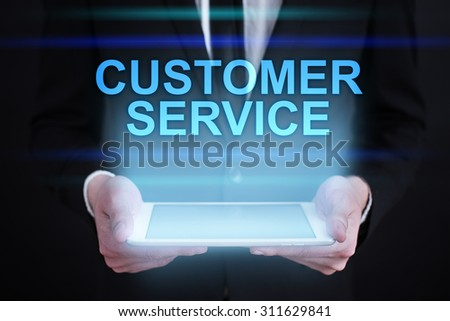 """Businessman holding a tablet pc with """"customer service"""" text on virtual screen.  Business concept.  - stock photo"""