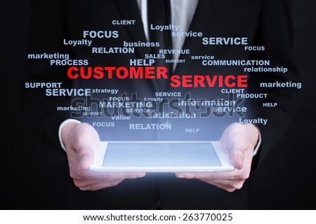 Businessman holding a tablet pc with customer service text on virtual screen. Internet concept. Business concept. - stock photo