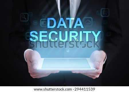 """Businessman holding a tablet pc with """"Data security"""" text on virtual screen. Internet concept. Business concept. - stock photo"""