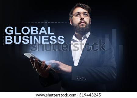 """Businessman holding a tablet pc with """"Global business"""" text on virtual screen. Business concept. - stock photo"""