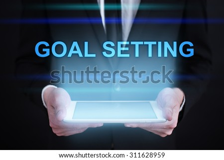 "Businessman holding a tablet pc with ""Goal setting"" text on virtual screen. Internet concept. Business concept."