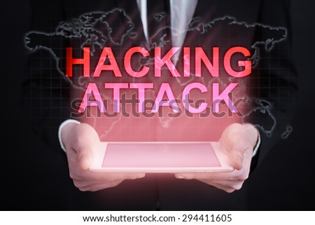 """Businessman holding a tablet pc with """"hacking attack"""" text on virtual screen. Internet concept. Business concept. - stock photo"""