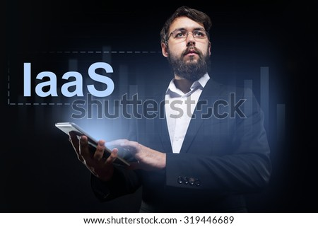"Businessman holding a tablet pc with ""IaaS"" text on virtual screen."