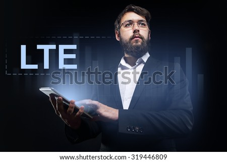 """Businessman holding a tablet pc with """"LTE"""" text on virtual screen. - stock photo"""