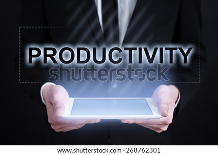 Businessman holding a tablet pc with productivity text on virtual screen. Internet concept. Business concept. - stock photo