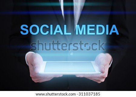 """Businessman holding a tablet pc with """"social media"""" text on virtual screen. Internet concept. Business concept. - stock photo"""
