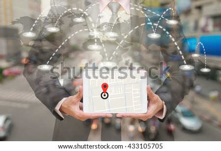 Businessman holding a tablet showing part of navigator map on connection line over the world map with blurred photo of traffic jam, Navigation concept,Elements of this image furnished by NASA - stock photo