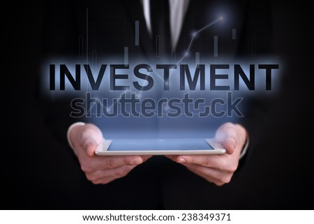 Businessman holding a tablet with a projected on-screen icon investment. business concept. Internet concept.  - stock photo